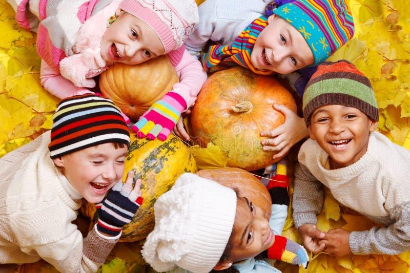 Малыши на желтых листьях стоковые изображения