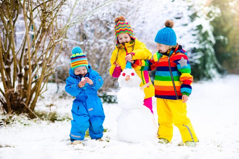 Малыши строя снеговик Дети в снежке управлять зимой розвальней потехи стоковая фотография rf