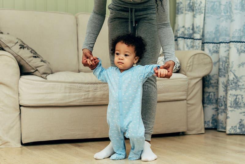 Малыш держа руки матери в живущей комнате стоковые изображения rf