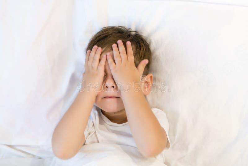Малыш лежит в кровати готовой для того чтобы спать Азиатский мальчик 3 лет идя спать дома eyes сонное стоковая фотография