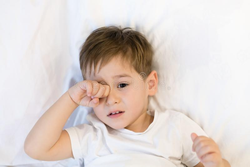 Малыш лежит в кровати готовой для того чтобы спать Азиатский мальчик 3 лет идя спать дома eyes сонное стоковое изображение