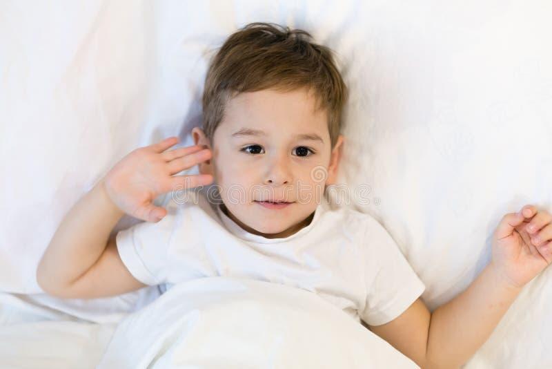 Малыш лежит в кровати готовой для того чтобы спать Азиатский мальчик 3 лет идя спать дома eyes сонное стоковое фото rf