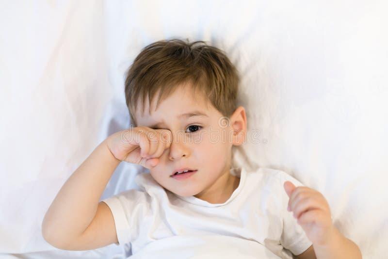 Малыш лежит в кровати готовой для того чтобы спать Азиатский мальчик 3 лет идя спать дома eyes сонное стоковая фотография rf