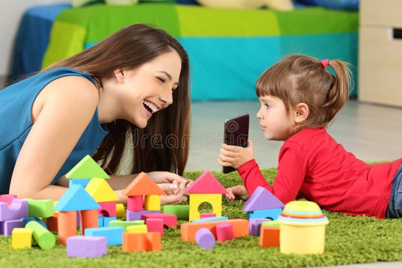 Малыш показывая телефон к ее матери стоковые фотографии rf