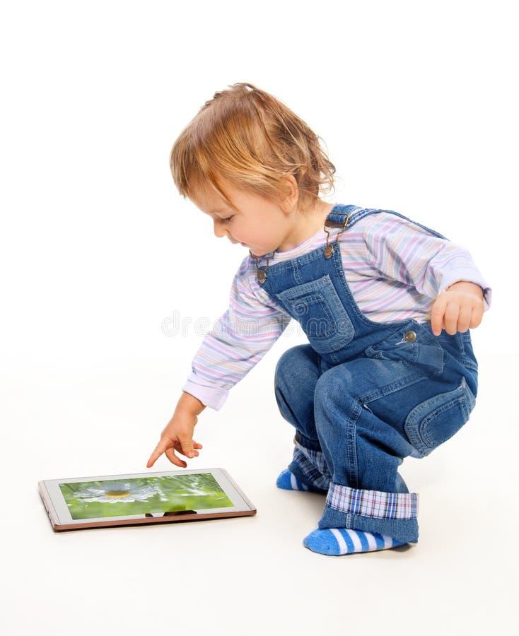 малыш таблетки ПК касатьясь детенышам стоковое изображение rf