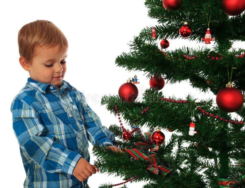 Малыш украшая рождественскую елку стоковое изображение
