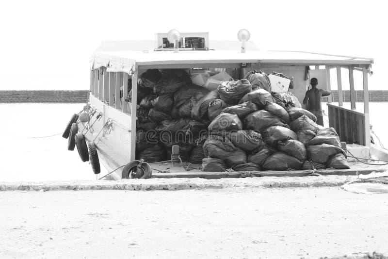 Мальдивский матрос носит мешки для мусора с его шлюпкой стоковая фотография