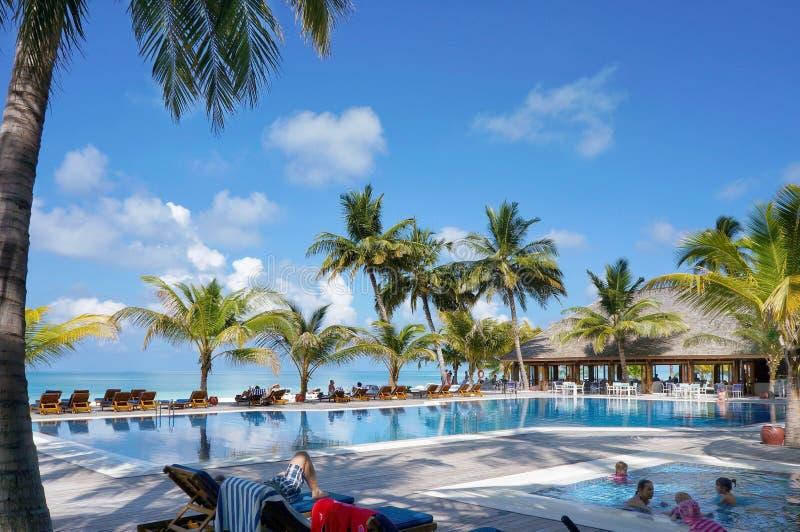 Мальдивы - 17-ое января 2013: Люди отдыхают и плавают в водном бассейне тропическим пляжем океана с пальмами и креслами для отдых стоковые изображения