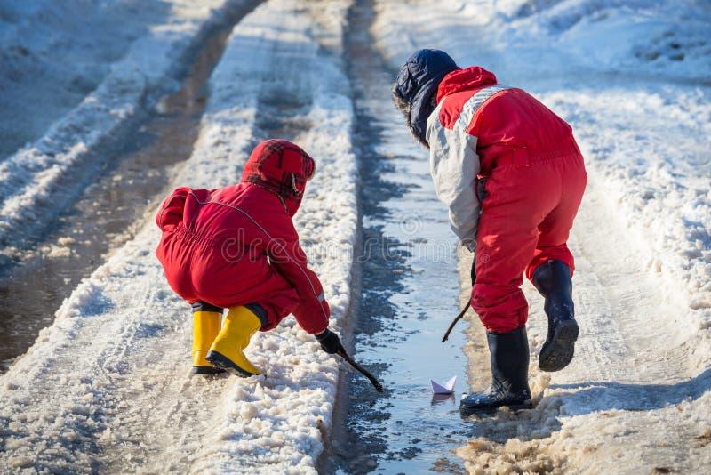 2 мальчика запуская бумажную шлюпку на The Creek стоковое изображение