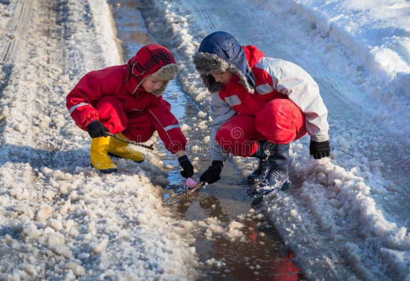 2 мальчика запуская бумажную шлюпку на The Creek стоковое фото