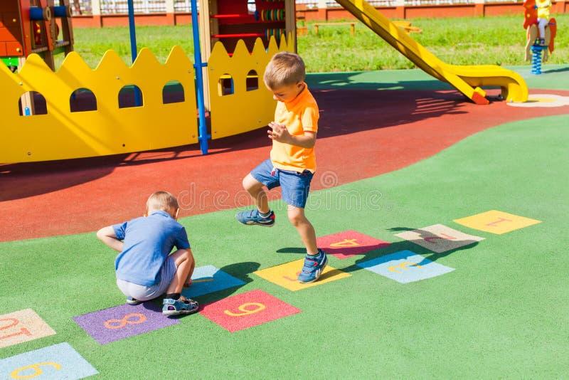 2 мальчика играя классики в лете outdoors стоковая фотография