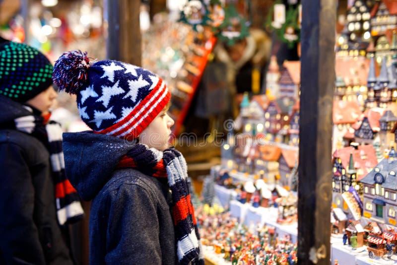 2 мальчика маленького ребенка выбирая украшение на рождественской ярмарке Красивые отпрыски и лучшие други ходя по магазинам для  стоковое фото rf