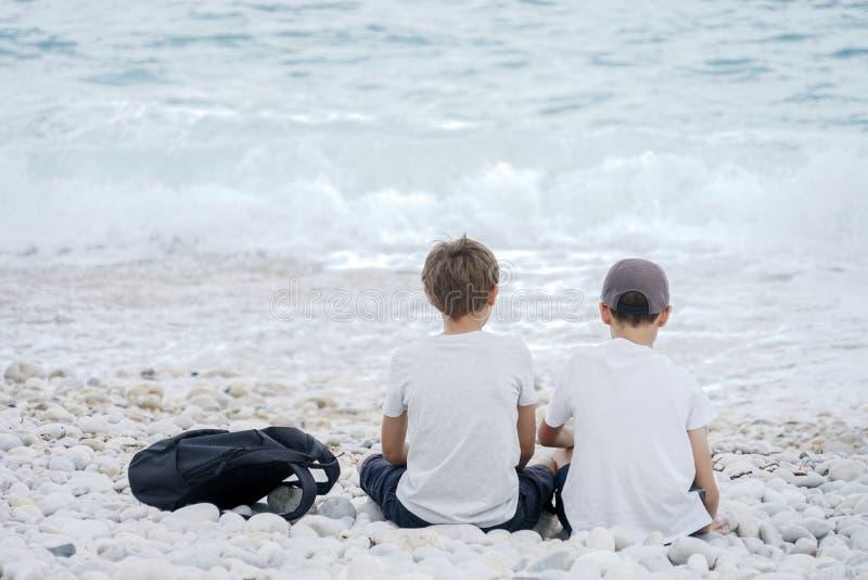 2 мальчика сидя рядом друг с другом на пляже морем стоковые изображения rf