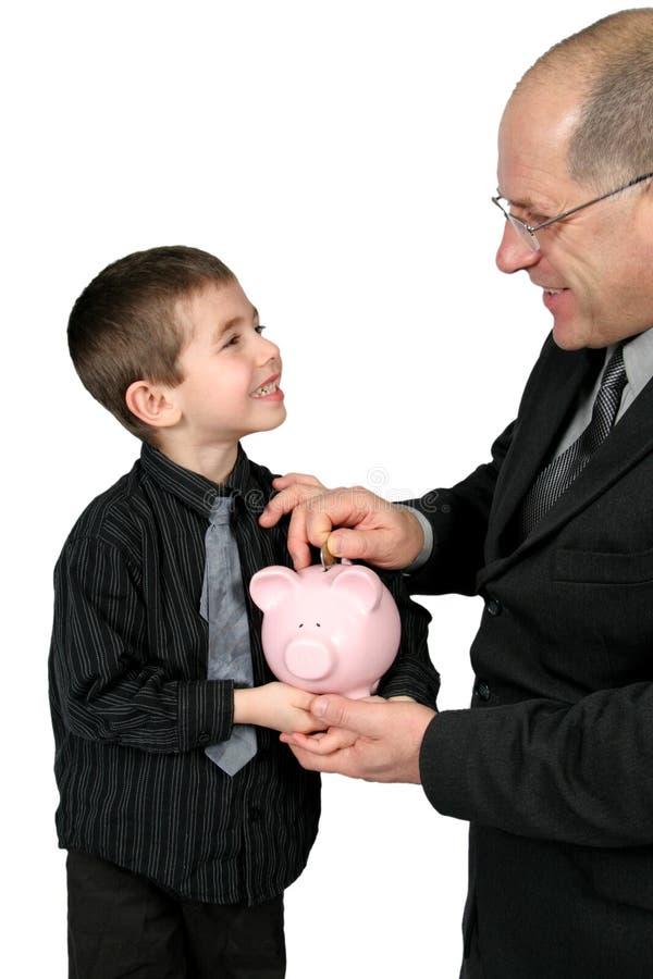 мальчики банка укомплектовывают личным составом класть дег piggy стоковые изображения rf