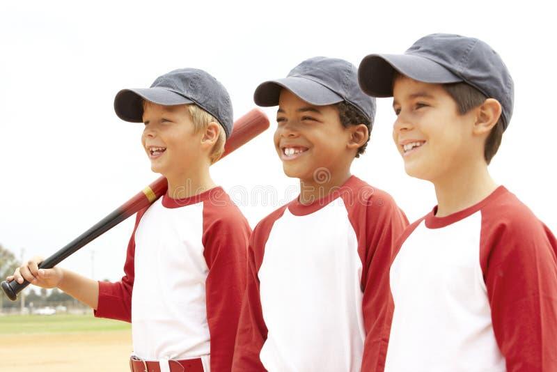 мальчики бейсбола объениняются в команду детеныши стоковое фото