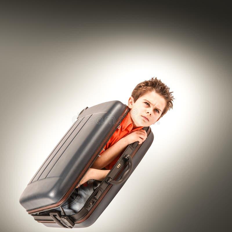 Мальчики запертые в чемодане стоковое изображение