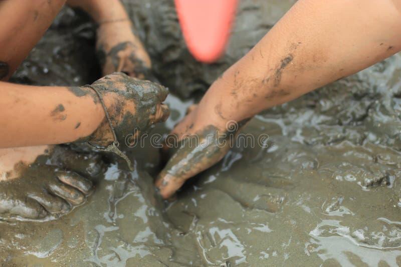 Мальчики ища раковины улитки на грязи морского дн дна стоковые фотографии rf