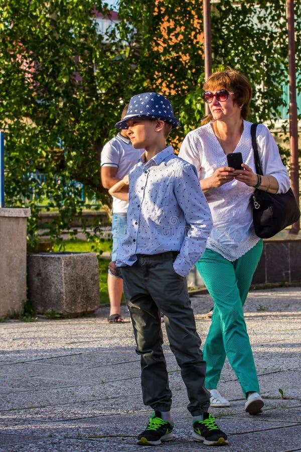 Мальчики и девушки бежать и скача двором Группа в составе дети играя красочные воздушные шары стоковое фото rf