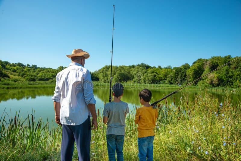 2 мальчики и деда пошли удить Они стоят на береге пруда и взгляда в расстояние стоковое фото rf