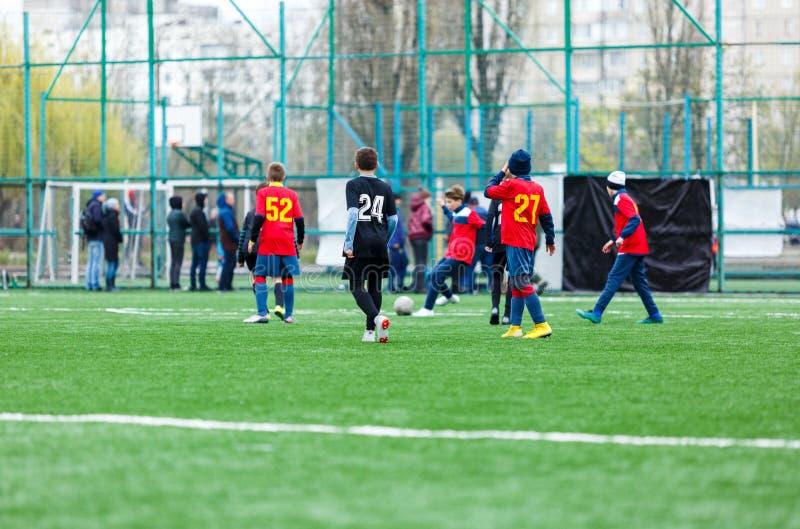 Мальчики на черном красном беге sportswear, капле, нападении на футбольное поле Молодые футболисты с шариком на зеленой траве r стоковая фотография