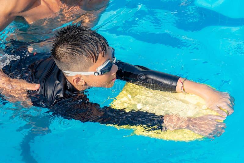 Мальчики плавают в бассейне стоковая фотография