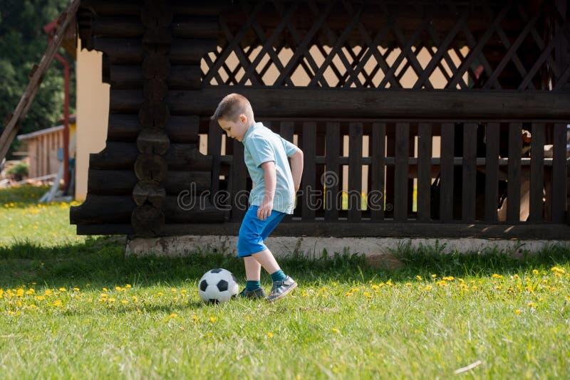 Мальчики подростков играя футбольный матч футбола Молодые футболисты бежать и пиная футбольный мяч на тангаже футбола стоковая фотография