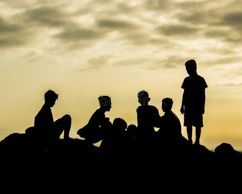 Мальчики силуэта вверху гора стоковое изображение