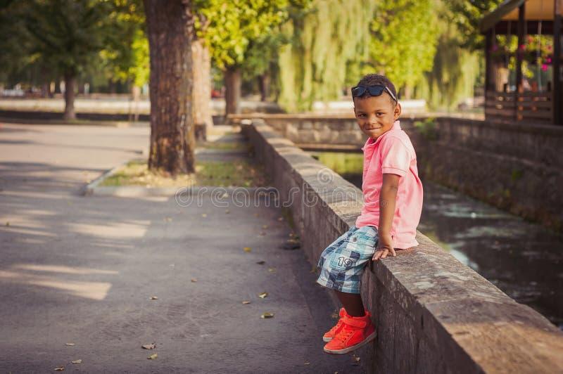 Мальчик Афро американский на спортивной площадке в парке стоковое фото