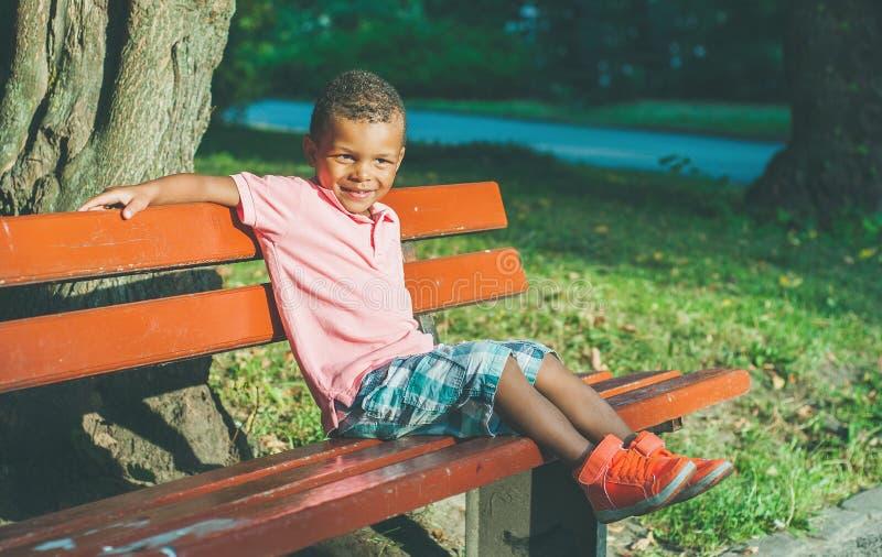 Мальчик Афро американский на спортивной площадке в парке стоковые изображения