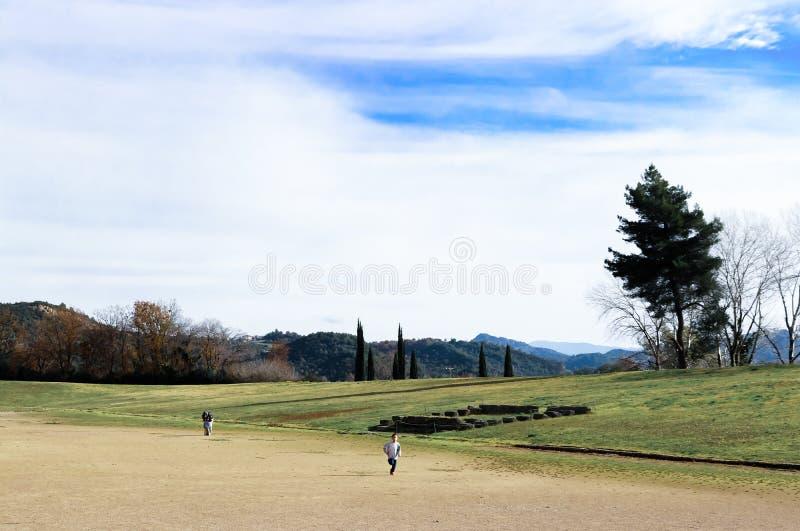 Мальчик бежать вниз с поля на месте первых игр Олимпиад пока его отец говорит к его брату за им Олимпию стоковое изображение