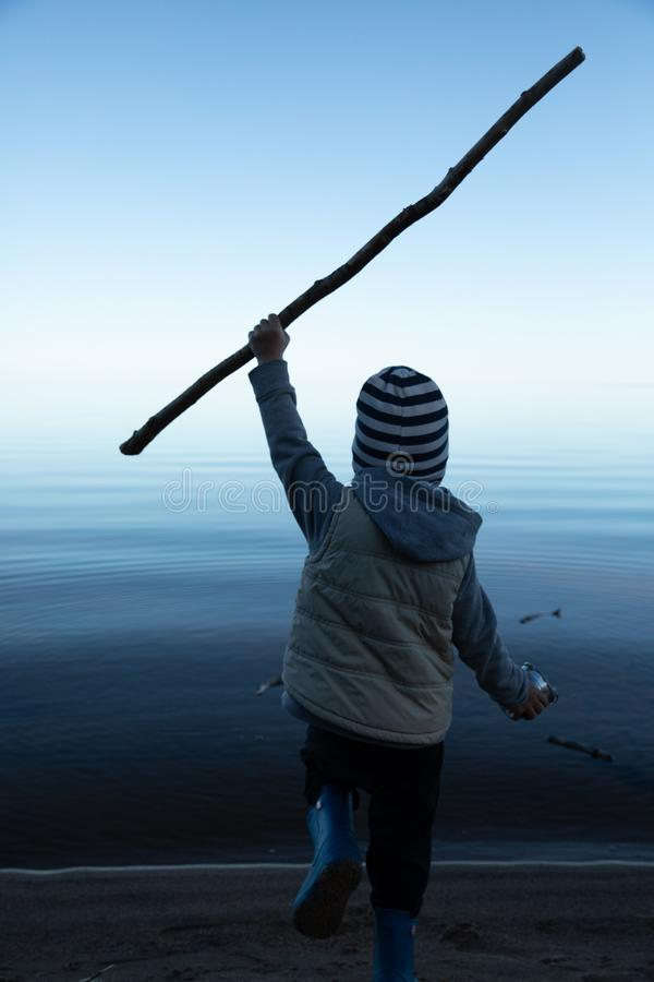 Мальчик бежит к воде с ручкой стоковая фотография