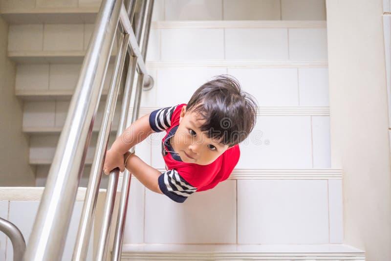 Мальчик взбирается вверх лестницы от сразу выше стоковая фотография rf