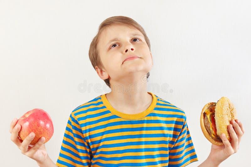 Мальчик выбирает между фаст-фудом и здоровым питанием на белой предпосылке стоковое фото rf