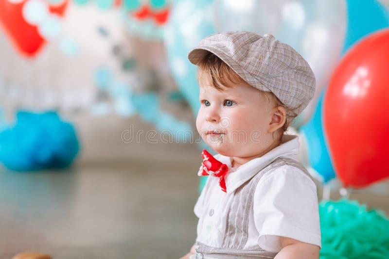 Мальчик выглядя бортовой с ртом предусматриванным в белых замороженности и торте в украшенном фоне студии Cakesmash дня рождения стоковое изображение