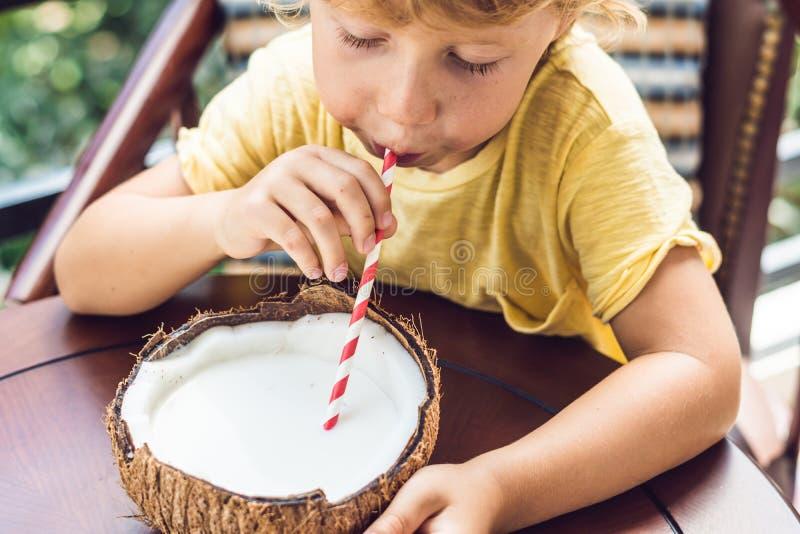 Мальчик выпивает домодельное молоко кокоса от половины кокоса стоковые изображения