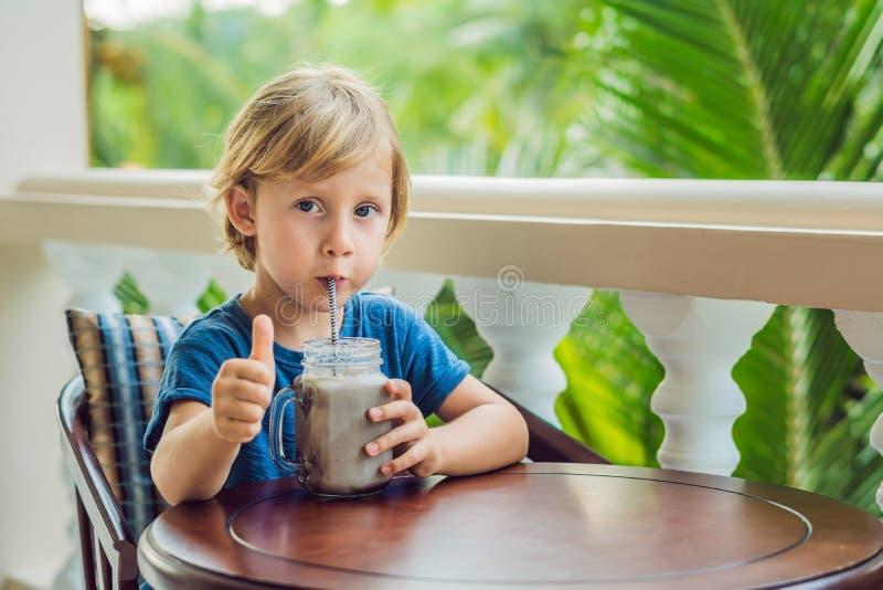 Мальчик выпивает питье от carob стоковые изображения
