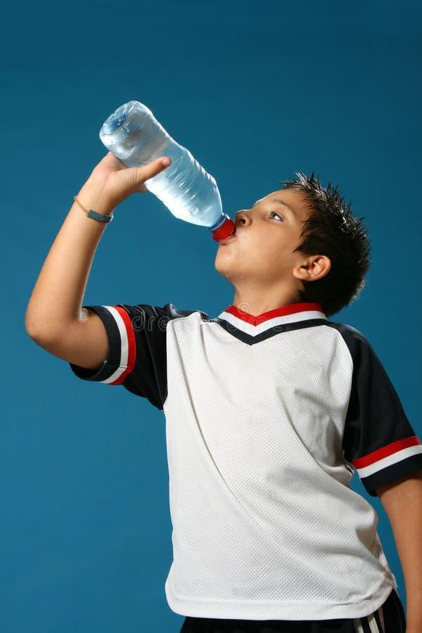 мальчик выпивая испытывающий жажду воду стоковое фото