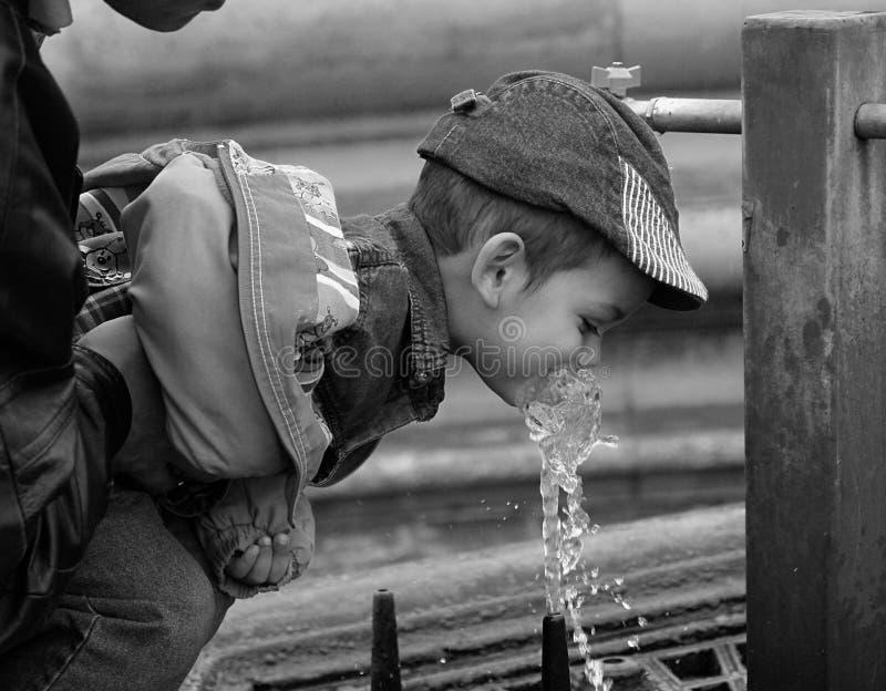 мальчик выпивая меньшюю воду стоковая фотография rf