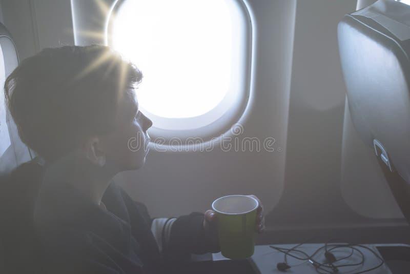 Мальчик выпивая от бумажного стаканчика сидя около окна самолета во время полета воздуха Еда служила на борту стоковое фото rf