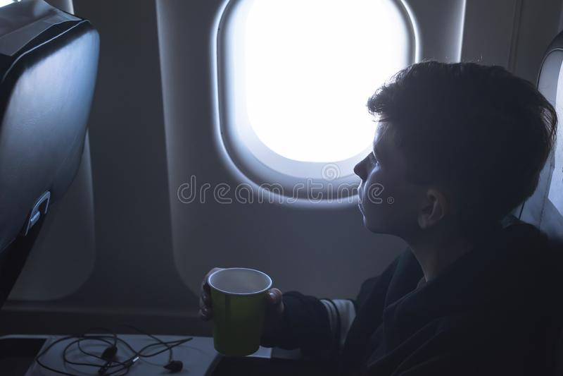 Мальчик выпивая от бумажного стаканчика сидя около окна самолета во время полета воздуха Еда служила на борту стоковое фото