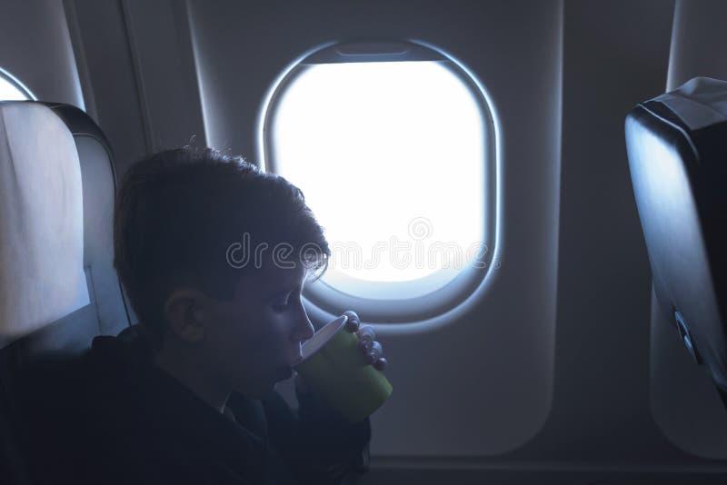 Мальчик выпивая от бумажного стаканчика сидя около окна самолета во время полета воздуха Еда служила на борту стоковое изображение