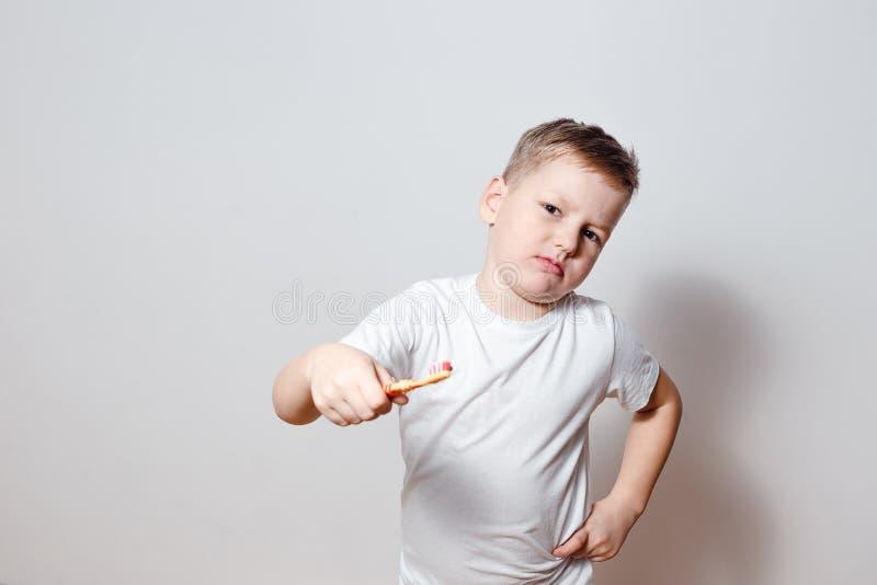 Мальчик в белой футболке не хочет чистить его зубы щеткой стоковое изображение