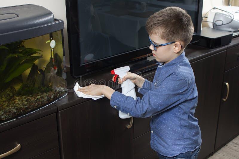 Мальчик в голубой рубашке и стеклах убирает комната Он обтирает пыль с белой тканью стоковое изображение