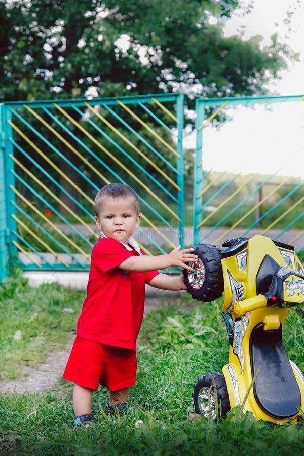 Мальчик в деревне ремонтирует большой автомобиль игрушки стоковое изображение rf