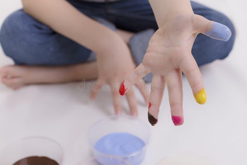 Мальчик в джинсах сидит на полу и грязно делает пальцы стоковое фото rf