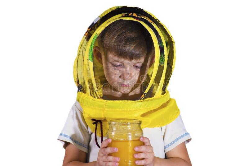 Мальчик в желтой маске от пчел, держа опарник меда и смотря мед в студии, на изолированной предпосылке стоковая фотография rf
