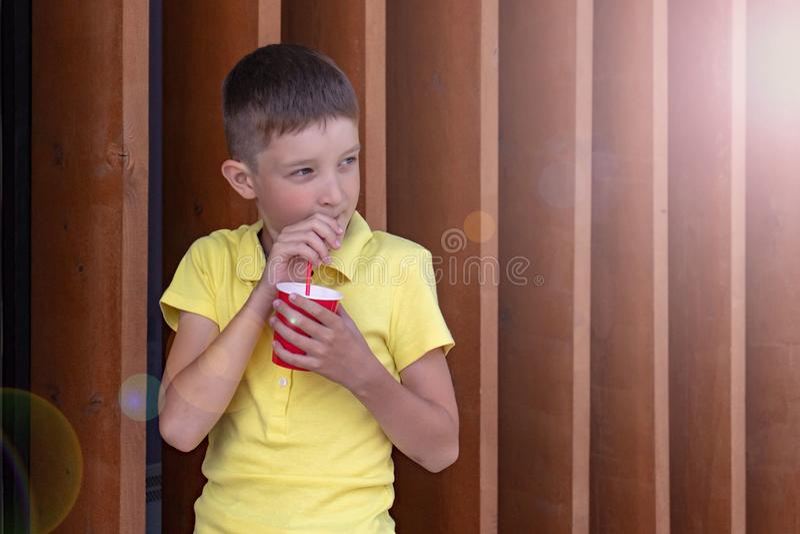 Мальчик в желтой рубашке стоя около деревянной стены, держа красный устранимый бумажный стаканчик и выпивая через солому стоковые фотографии rf