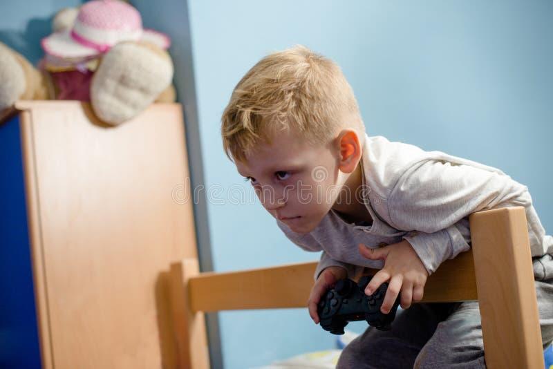 Мальчик в комнате играя видеоигры стоковая фотография