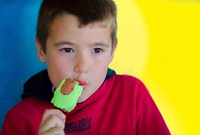Мальчик в красном цвете наслаждается мороженым арахис-шоколада на голубом и желтом b стоковое изображение rf
