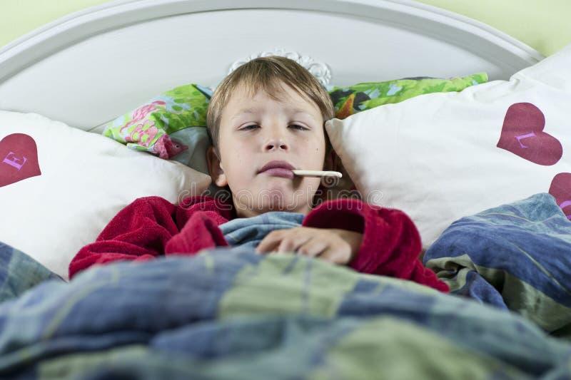 Мальчик в кровати с гриппом стоковое изображение